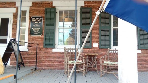 The porch and front entrance to the museum show a flag and a sign with a few chairs to sit in.