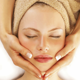A lady with a towel wrapped around her hair receives a facial from a spa atendant.