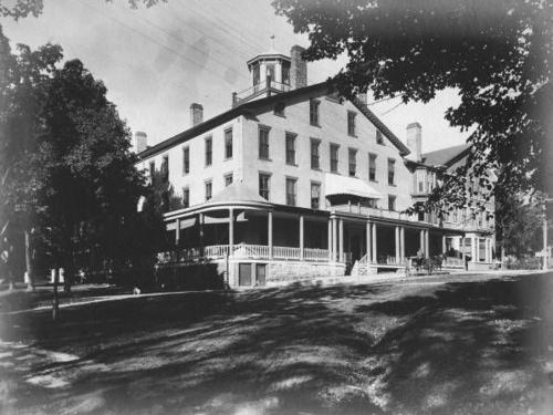 A black and white historic images of the Inn shows the exterior of the building from a street view.