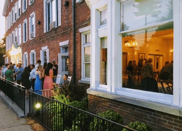 The outside of the Inn shoes a gathering of people on the porch.