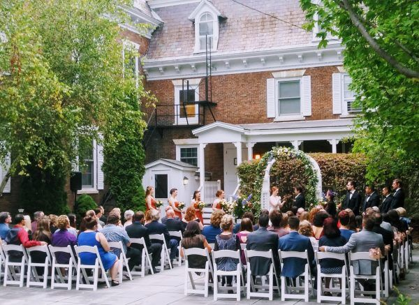 A wedding takes place in out courtyard. The bride and groom stand under a alter and rows of people water