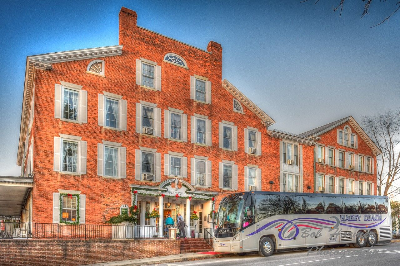 A large tour bus is parked outside of the Inn.