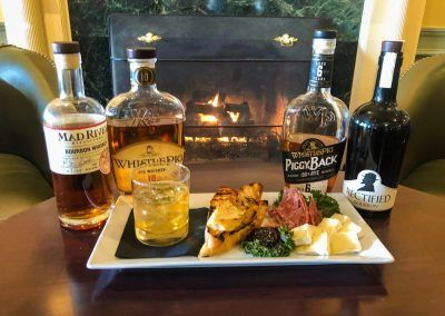 A plate with a meat and cheese sits in front of four bottles of whisky.