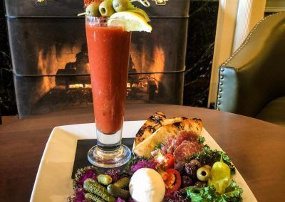 A plate with meat and cheese sit with a tall bloody mary.